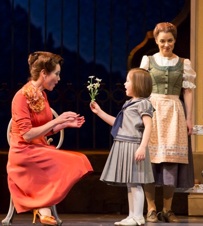 Baroness Schraeder (Elizabeth Futral) accepts a flower from Gretl (Nicole Scimeca) as Maria (Jenn Gambatese) beams proudly. Sound of Music Lyric Opera Chicago 2013 (Todd Rosenberg)